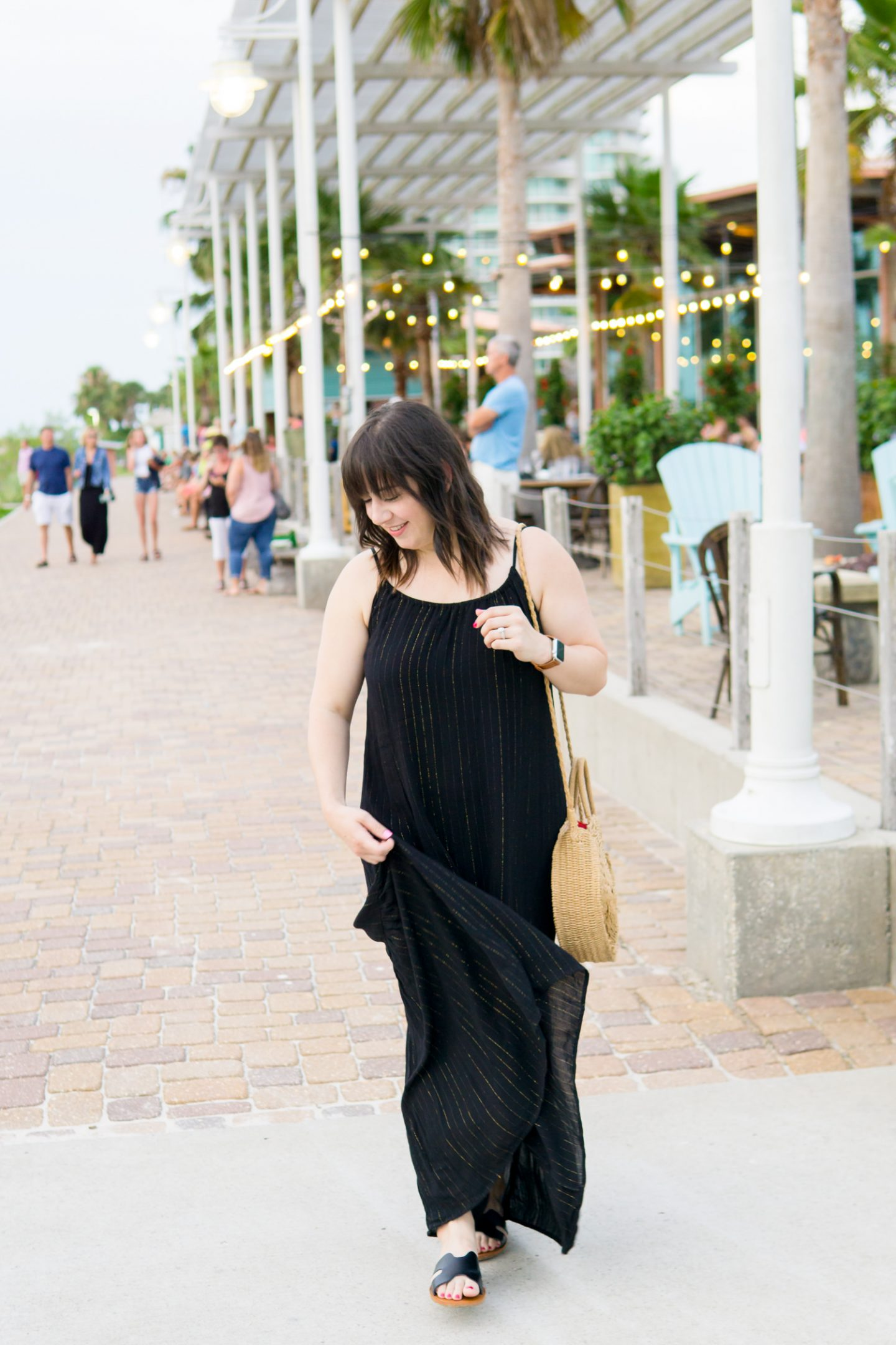 a photo of a young woman outside a beach restaurant in a black date night dress